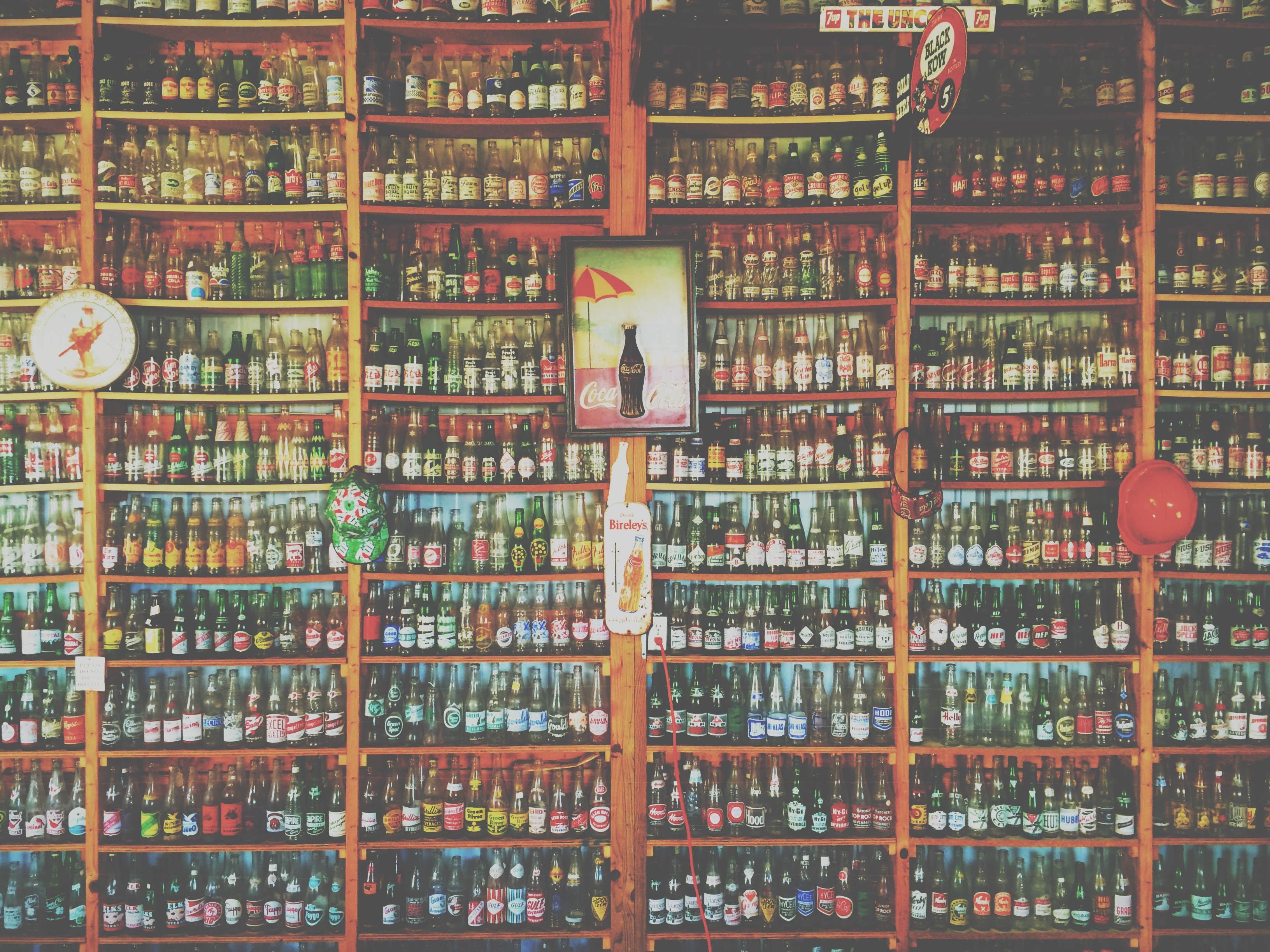 A collection of vintage Coca-Cola bottles on a large shelf.