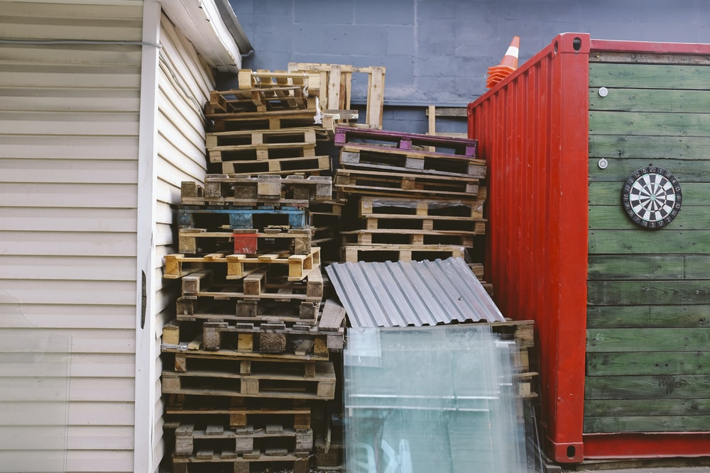 646bda89da brown wooden crate lot between red and green shipment container