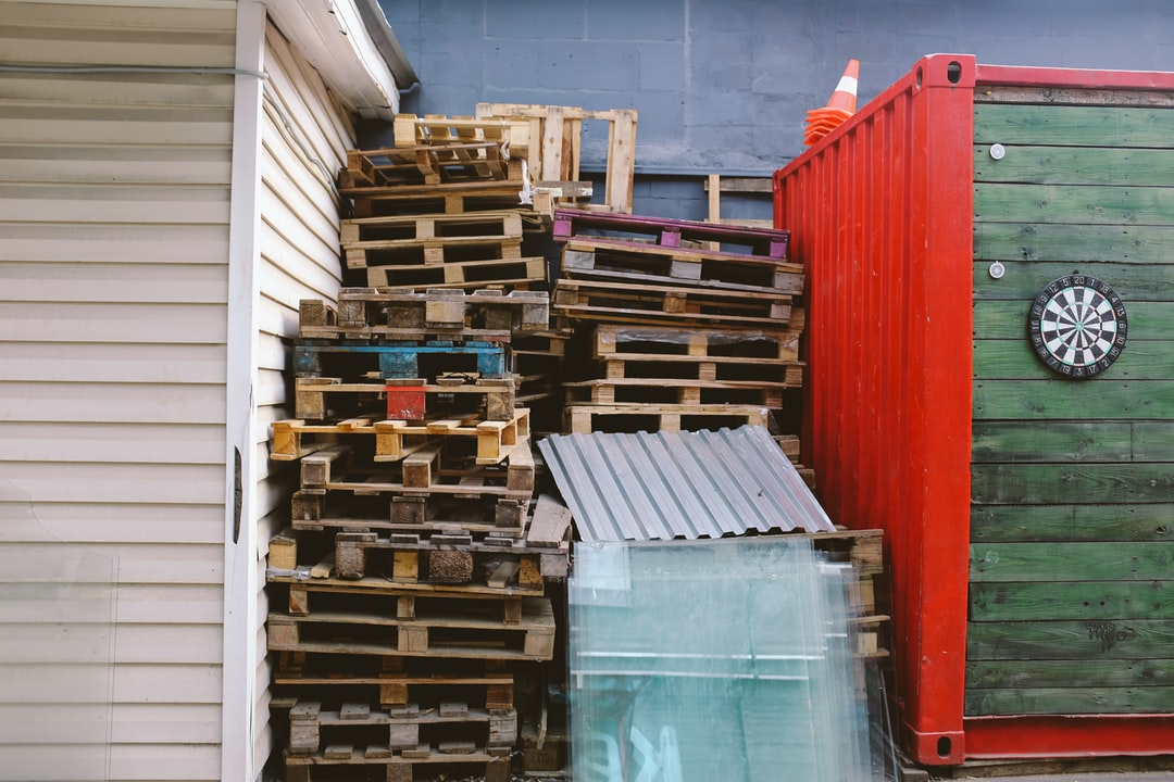 Pallets stacked by garbage