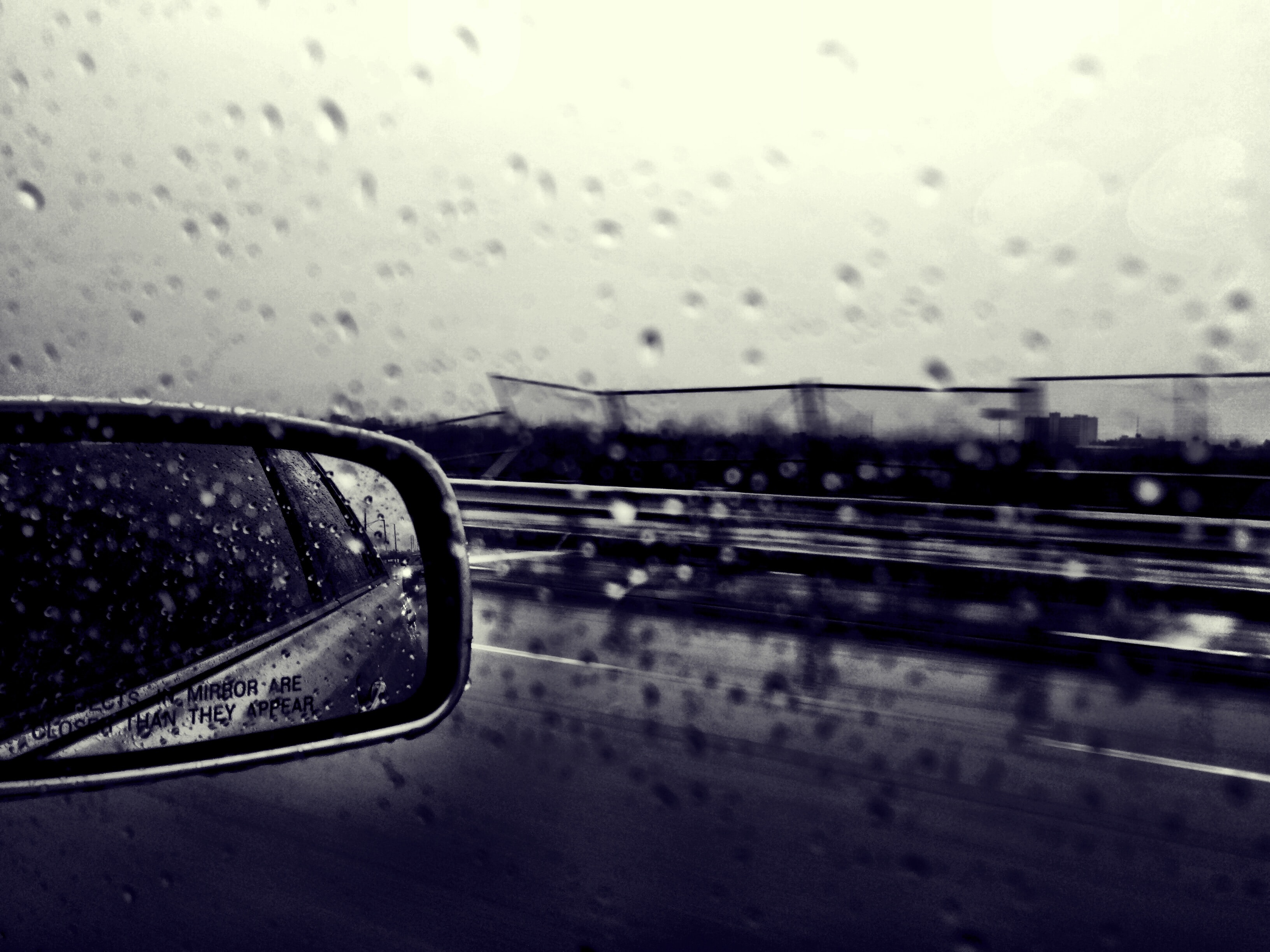 Black and white shot of car wing mirror and window reflection with rain droplets and road