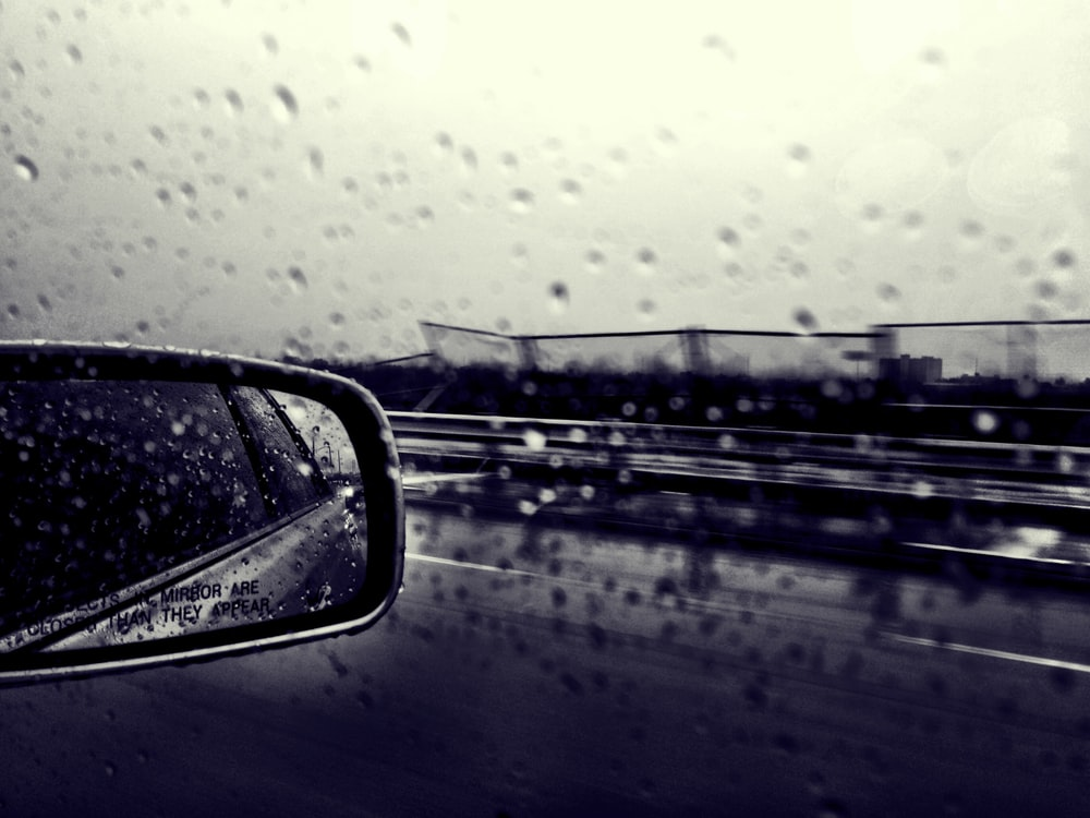 selective focus grayscale photography of side mirror and windshield with water dew