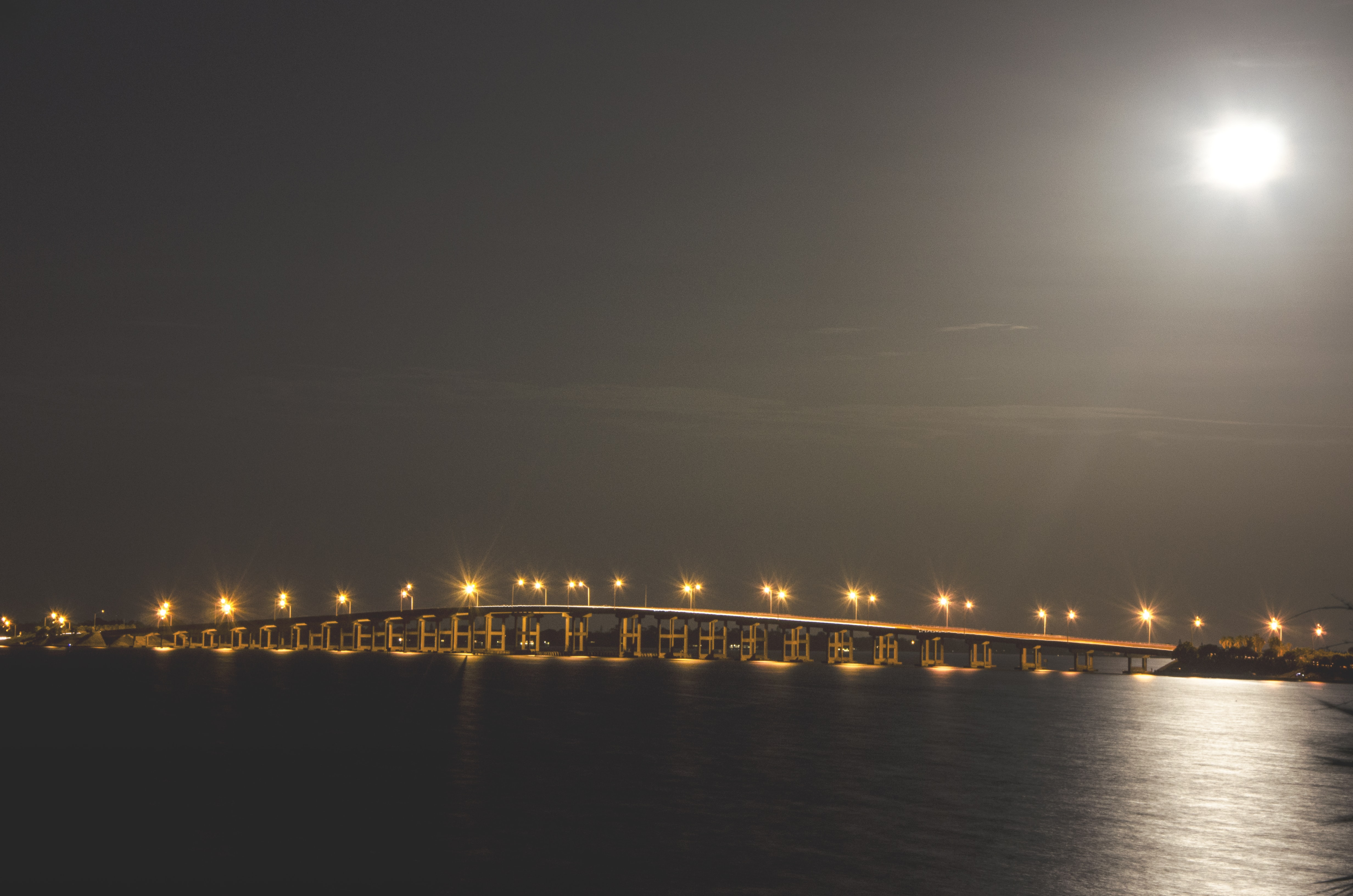 A well-lit bridge at night across the waters under the bright moonlight