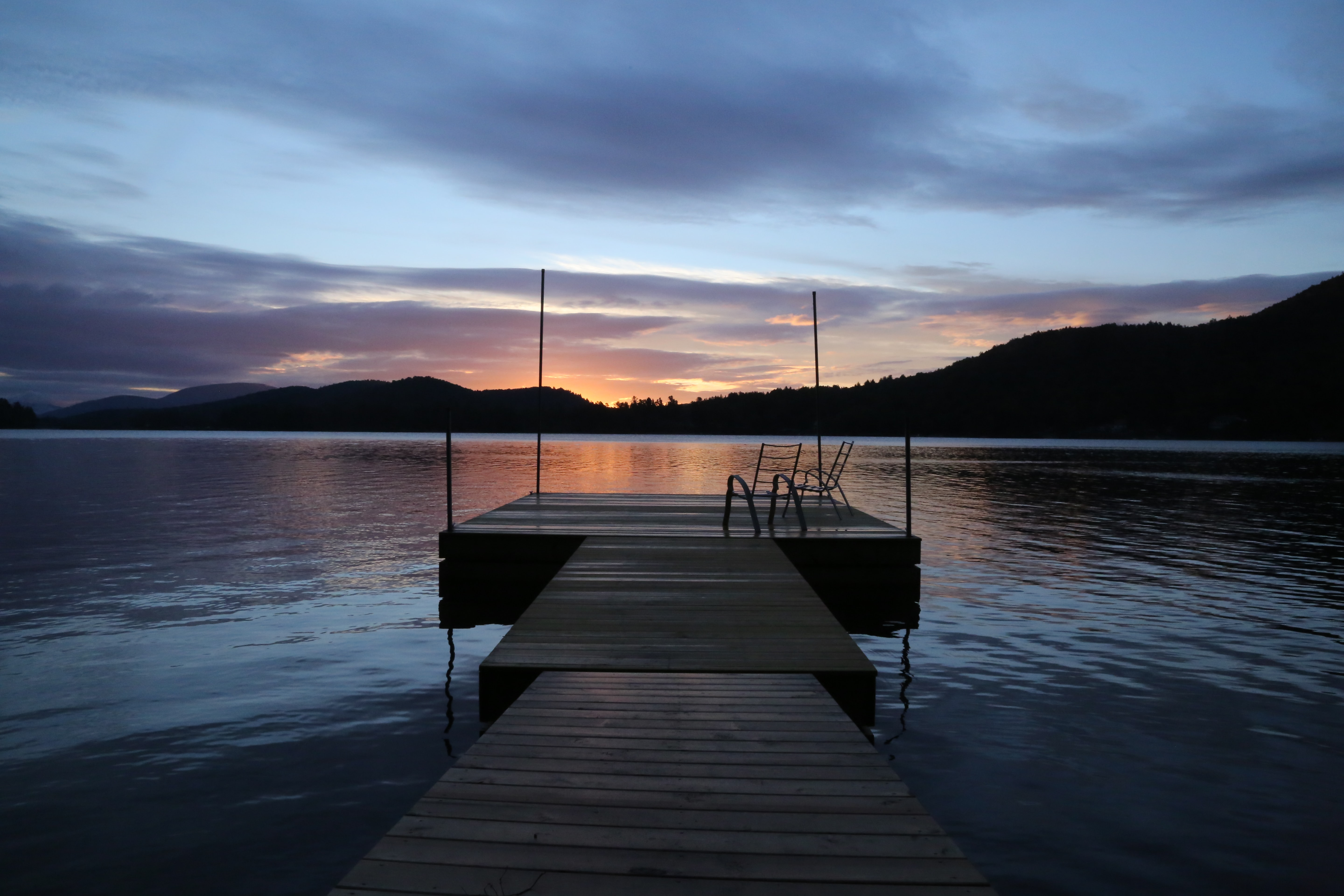 Looking out towards the end of a dock over a lake at sunset