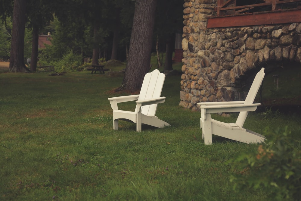 two white wooden armchairs on grasses