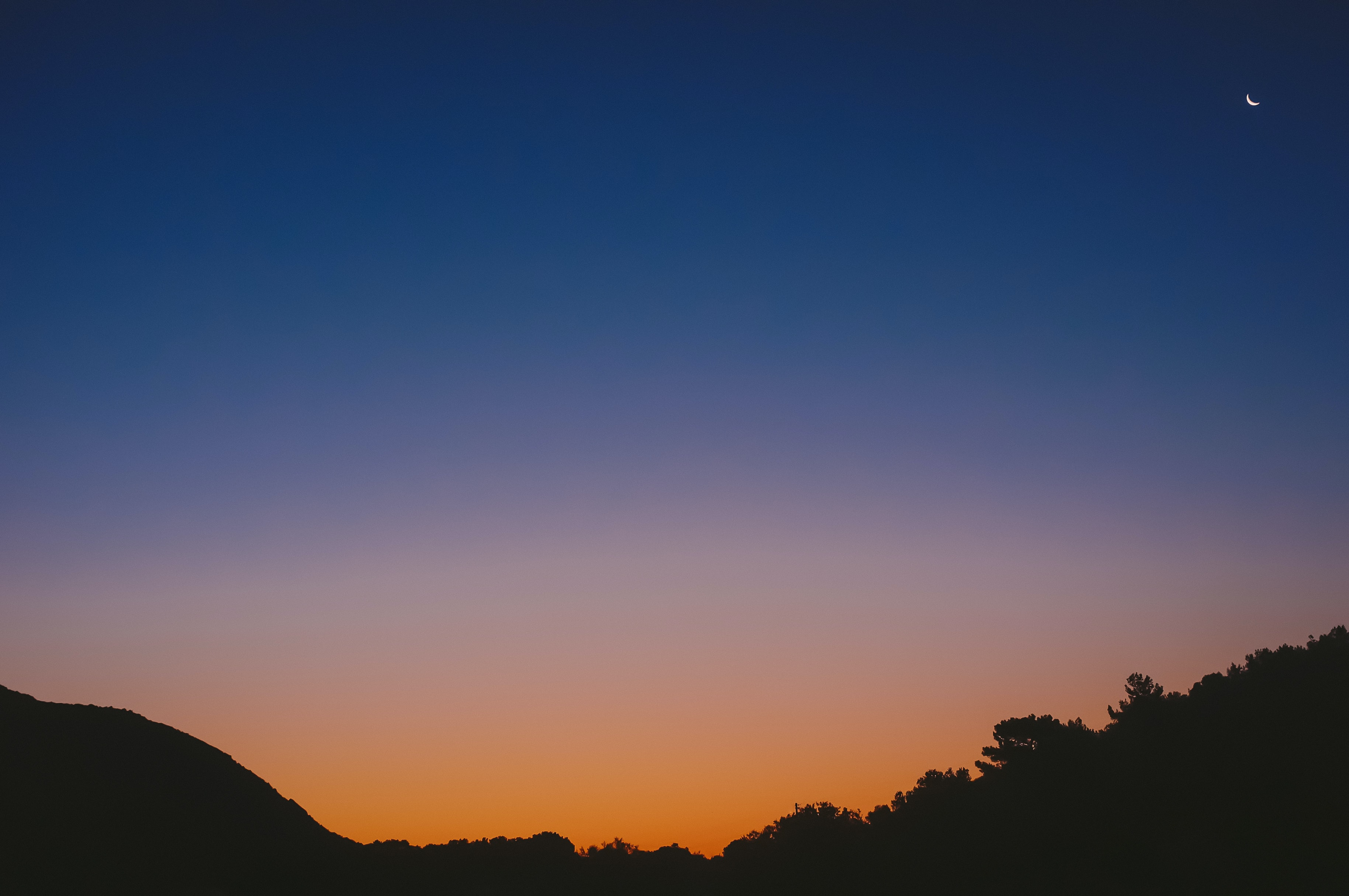 Small crescent moon rises in the twilight glow of the sky
