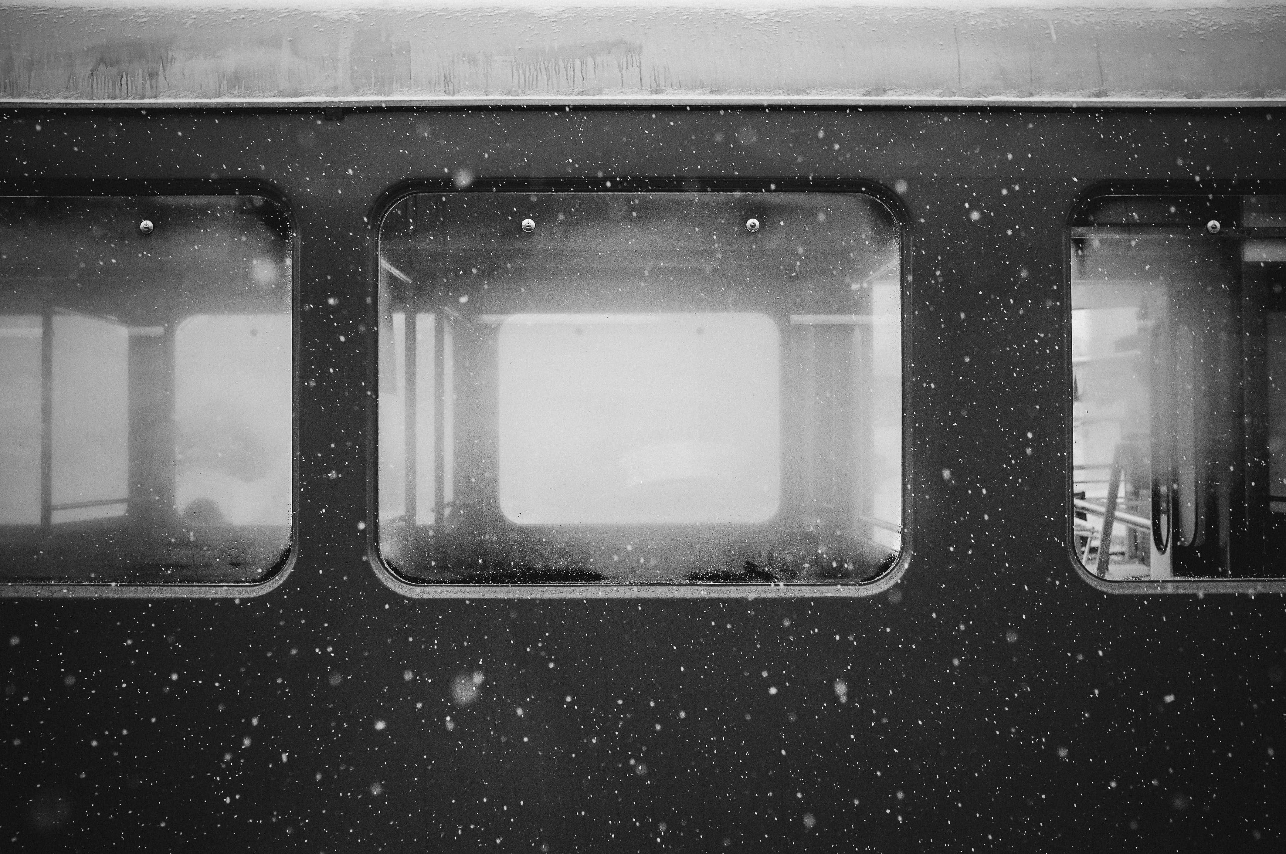Black and white shot of train carriage window with falling snow