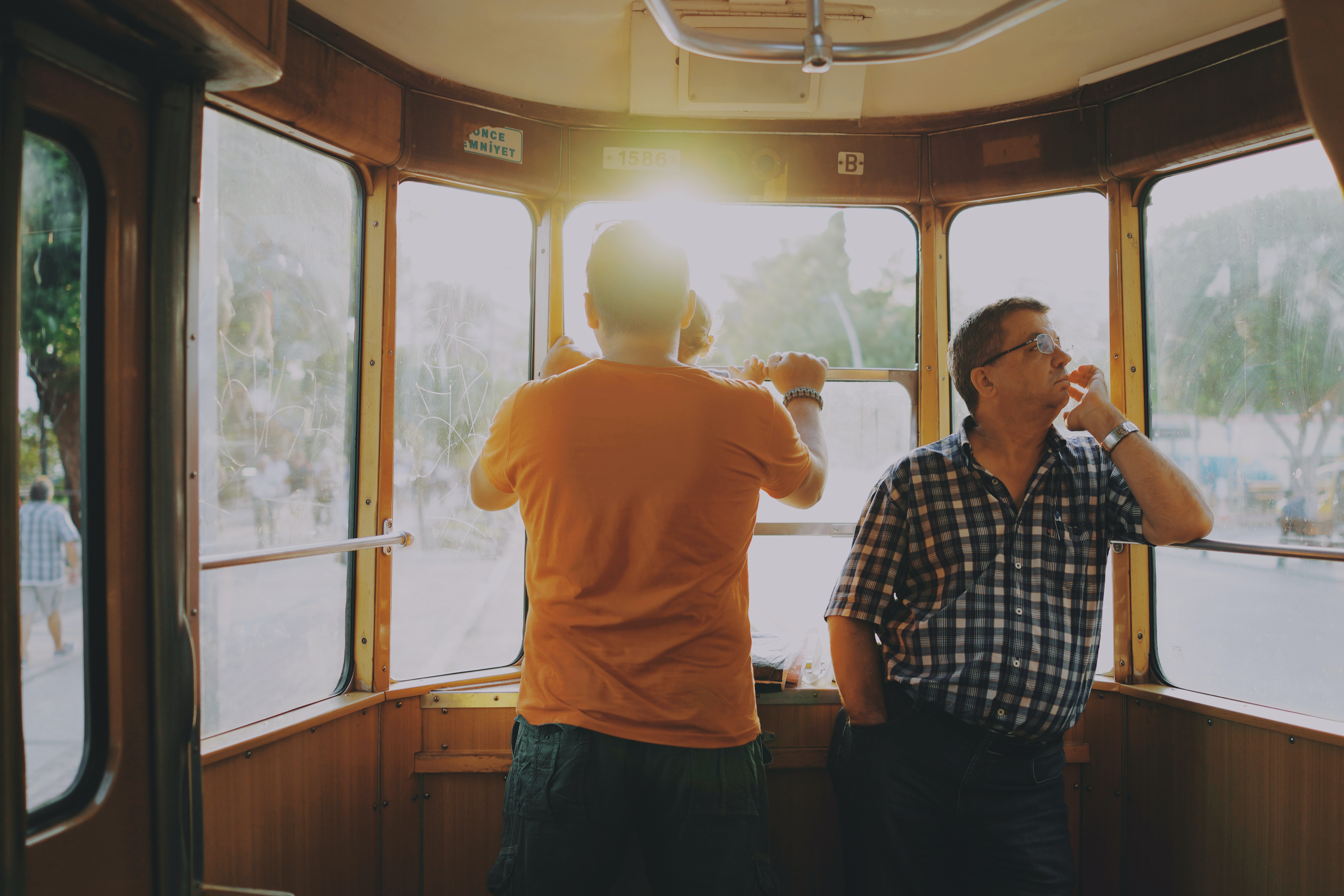 Two men wearing watches standing in a streetcar while watching the sun rise over a street