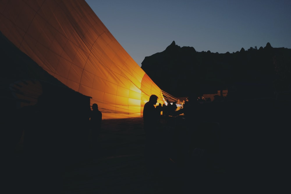 silhouette photo of people sitting near orange cover