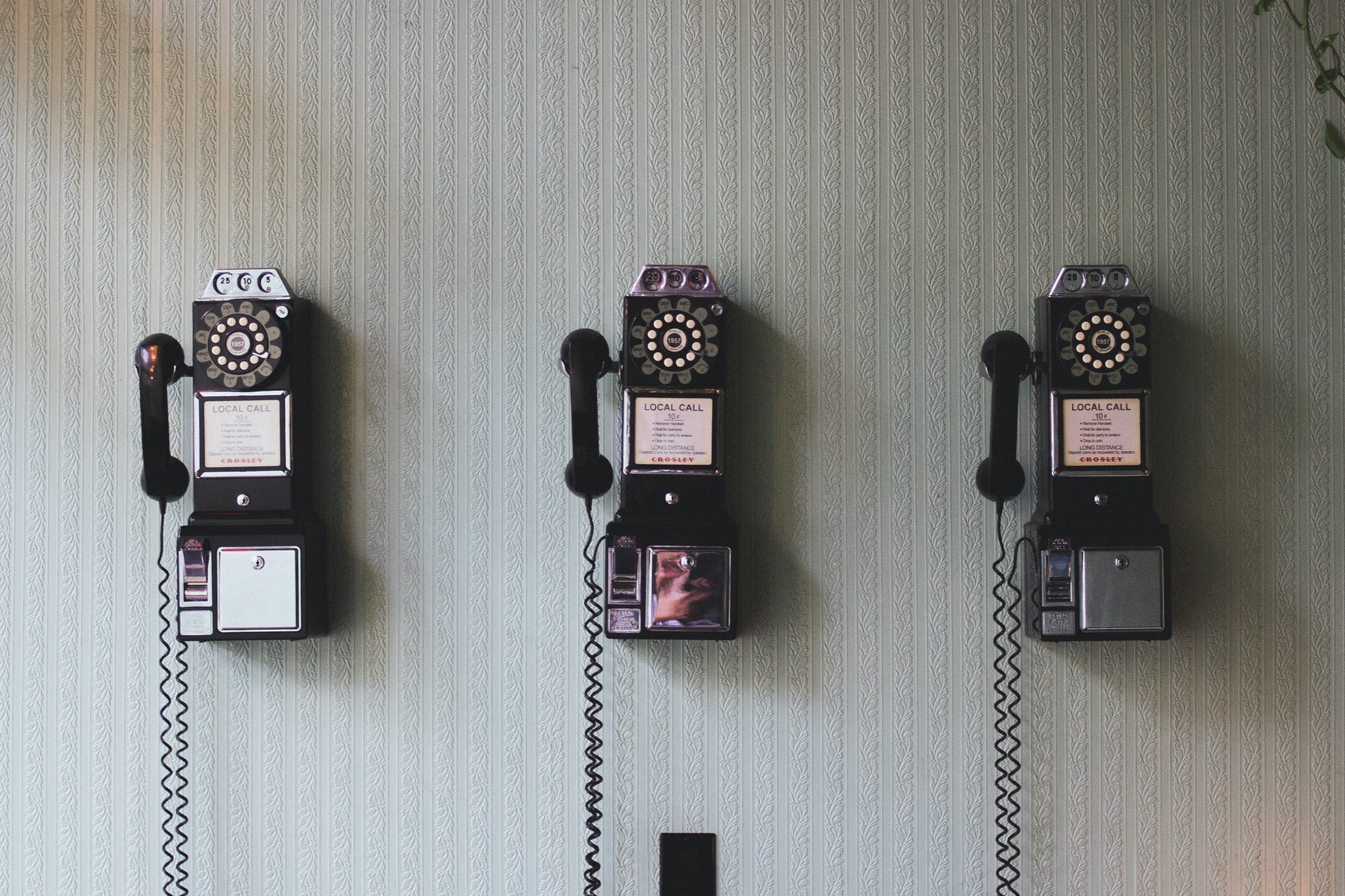 Image of three phone devices next to each other with a cord drilled into the wall.