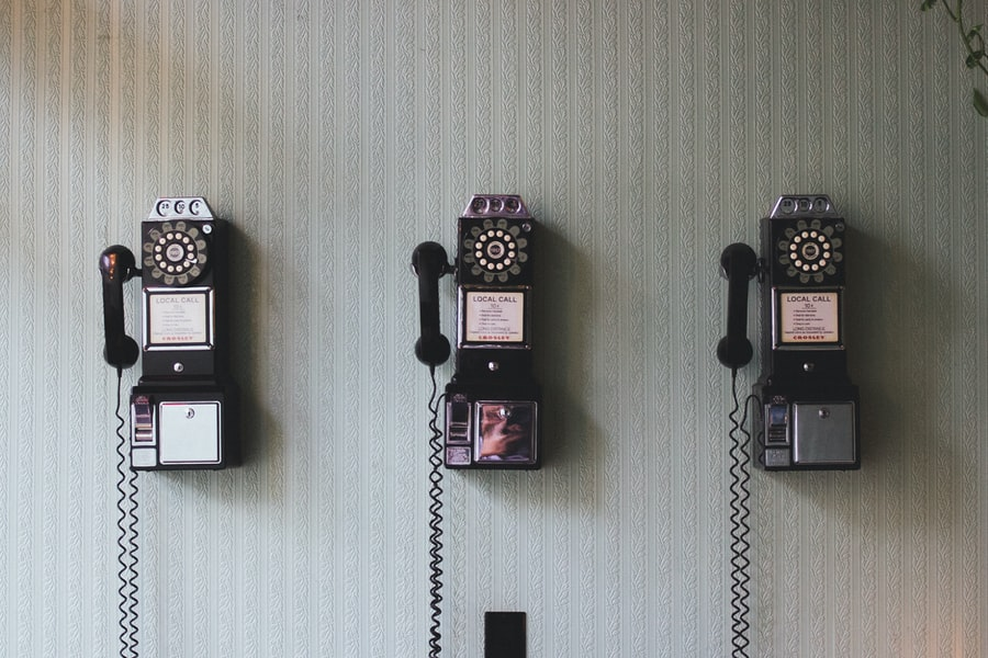 A set of vintage telephones hang on a wall.