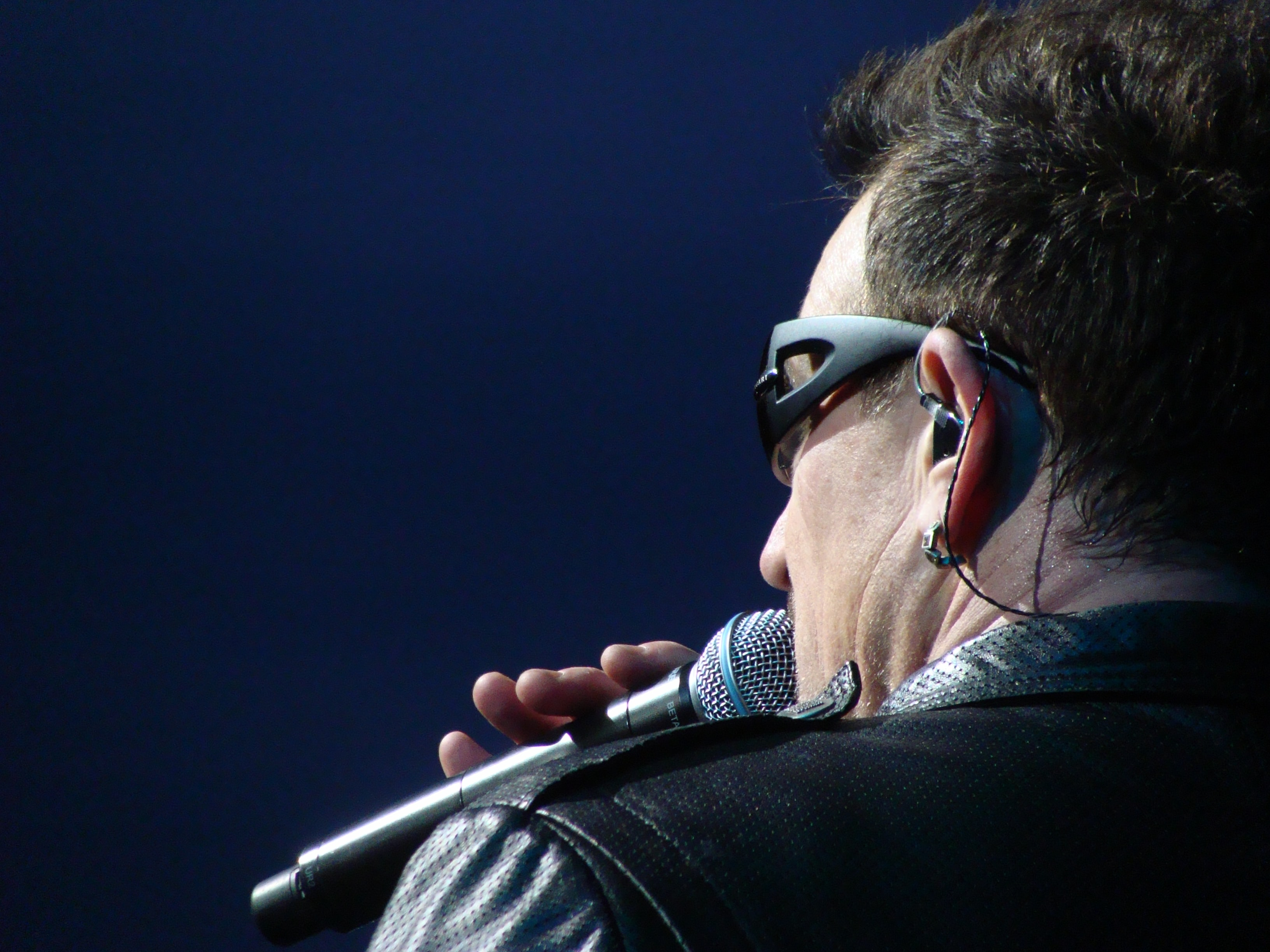 Singer Bono hold microphone and wears glasses and earpiece during a concert