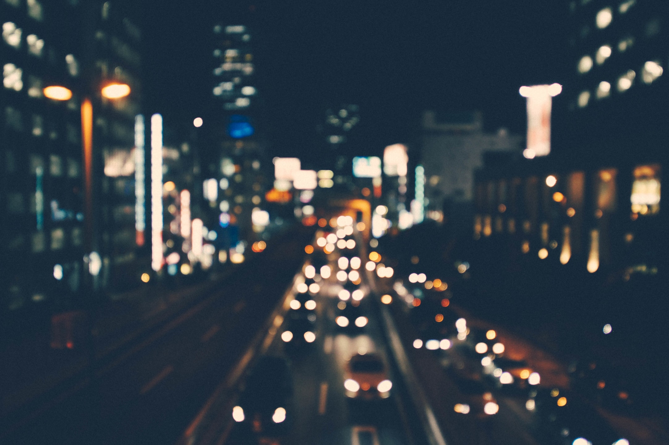 A blurry shot of a city street lit up by buildings and cars at night