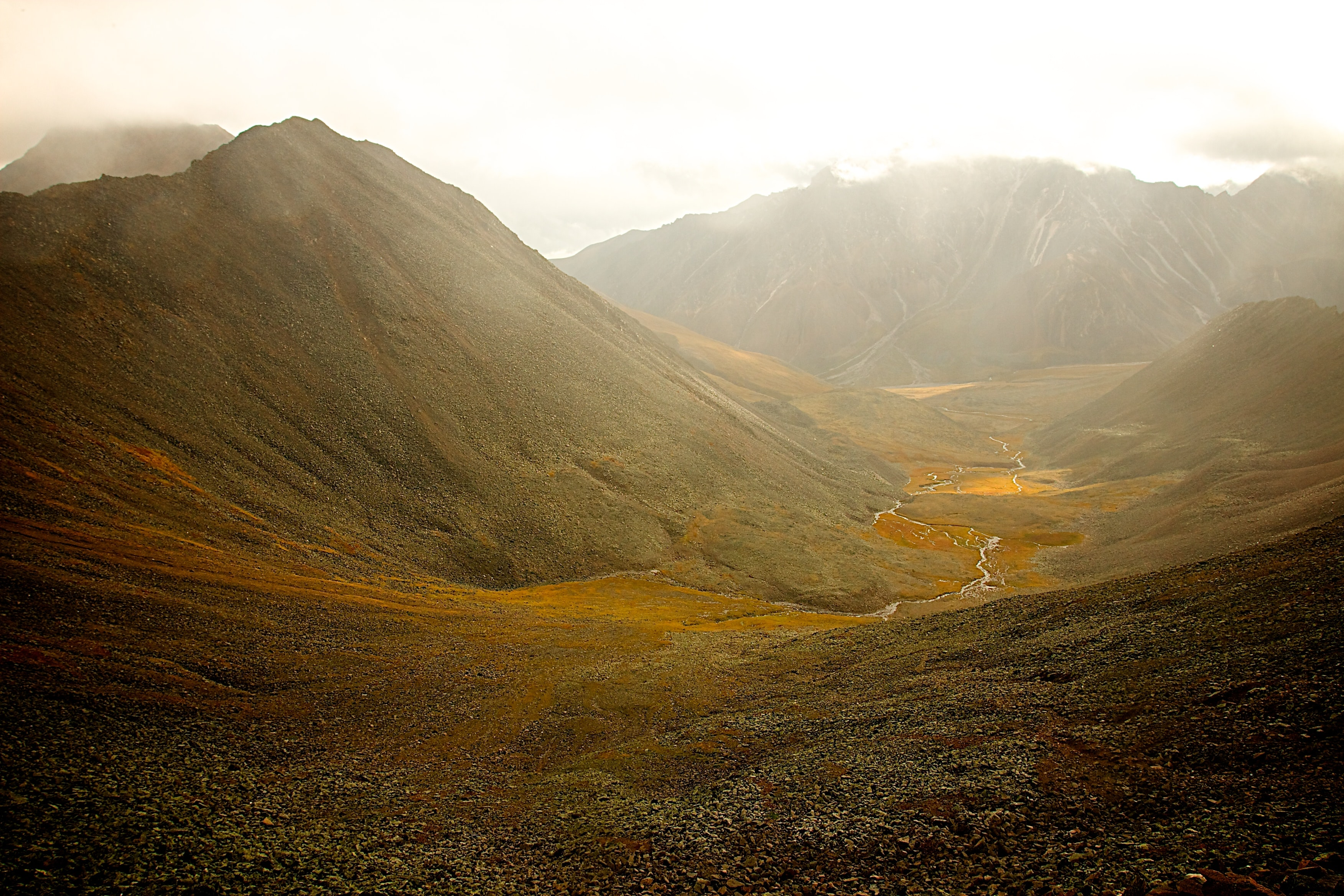 A yellow and brown mountain valley with a narrow stream on its floor