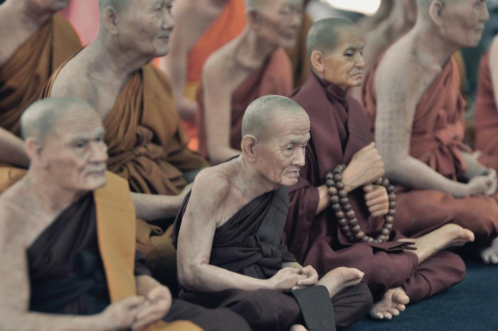 monks sitting on floor while praying