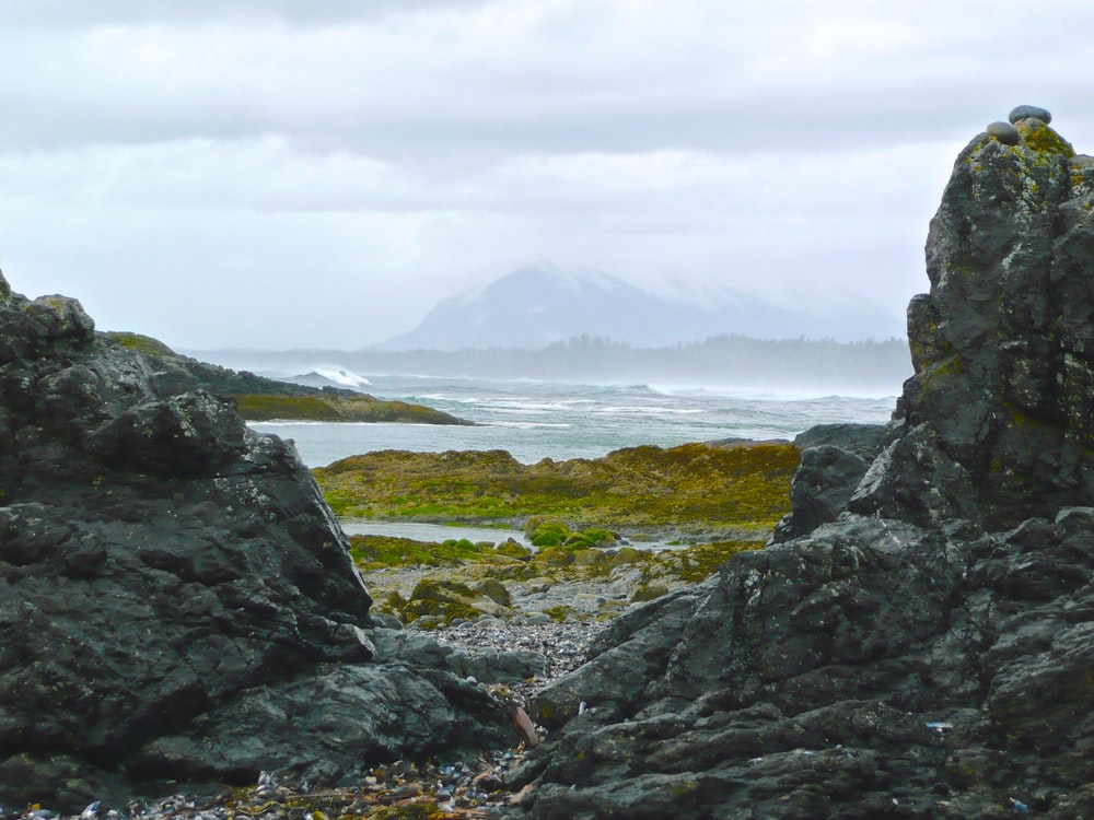 gray rock formations in front body of water