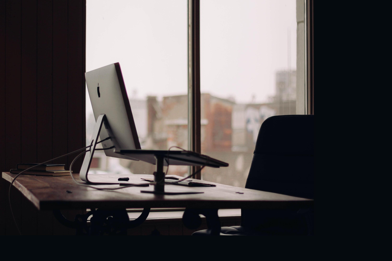 A desk in an dark office workspace showing mac apple computer near a window