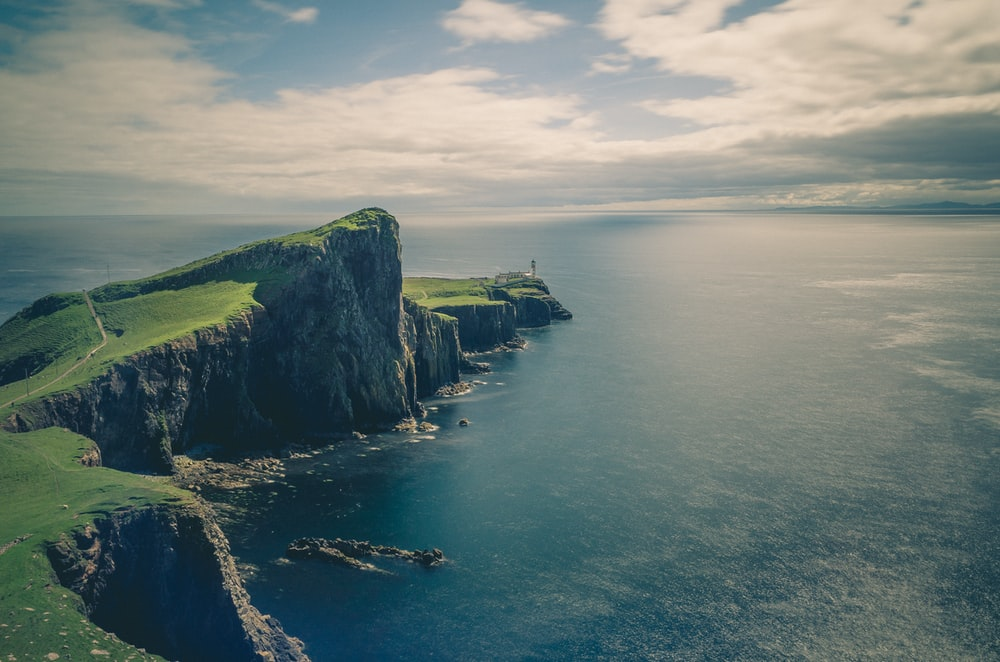sea and rock cliff with grasses under cloudy sky