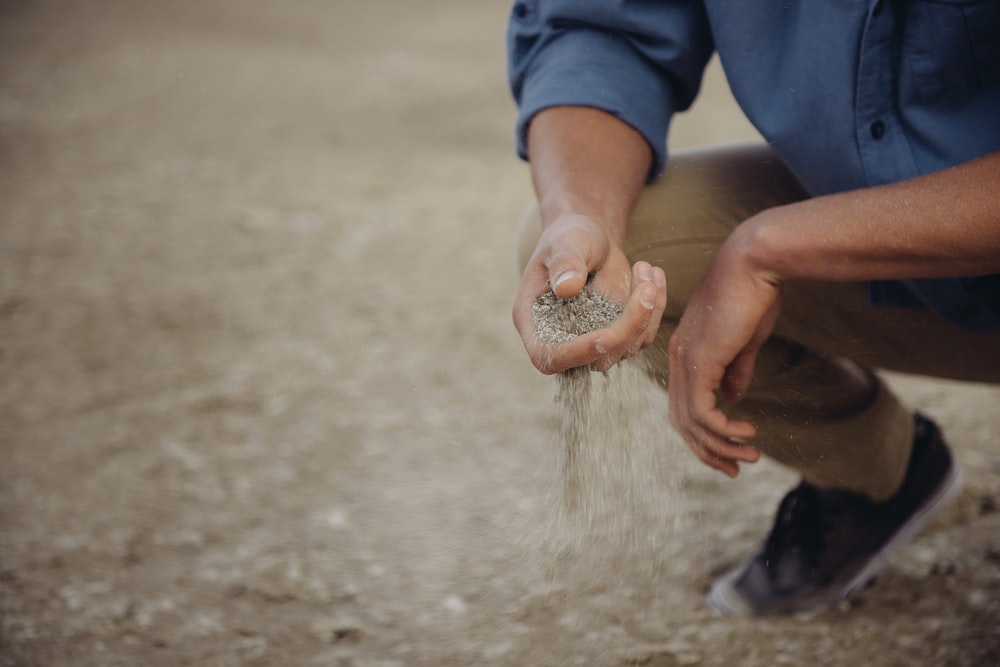 Person crouches down with a handful of sand that slips through their fingers