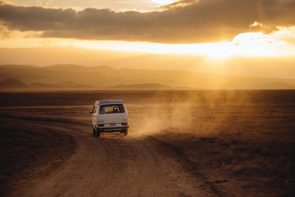 white vehicle traveling desert land field during sunset