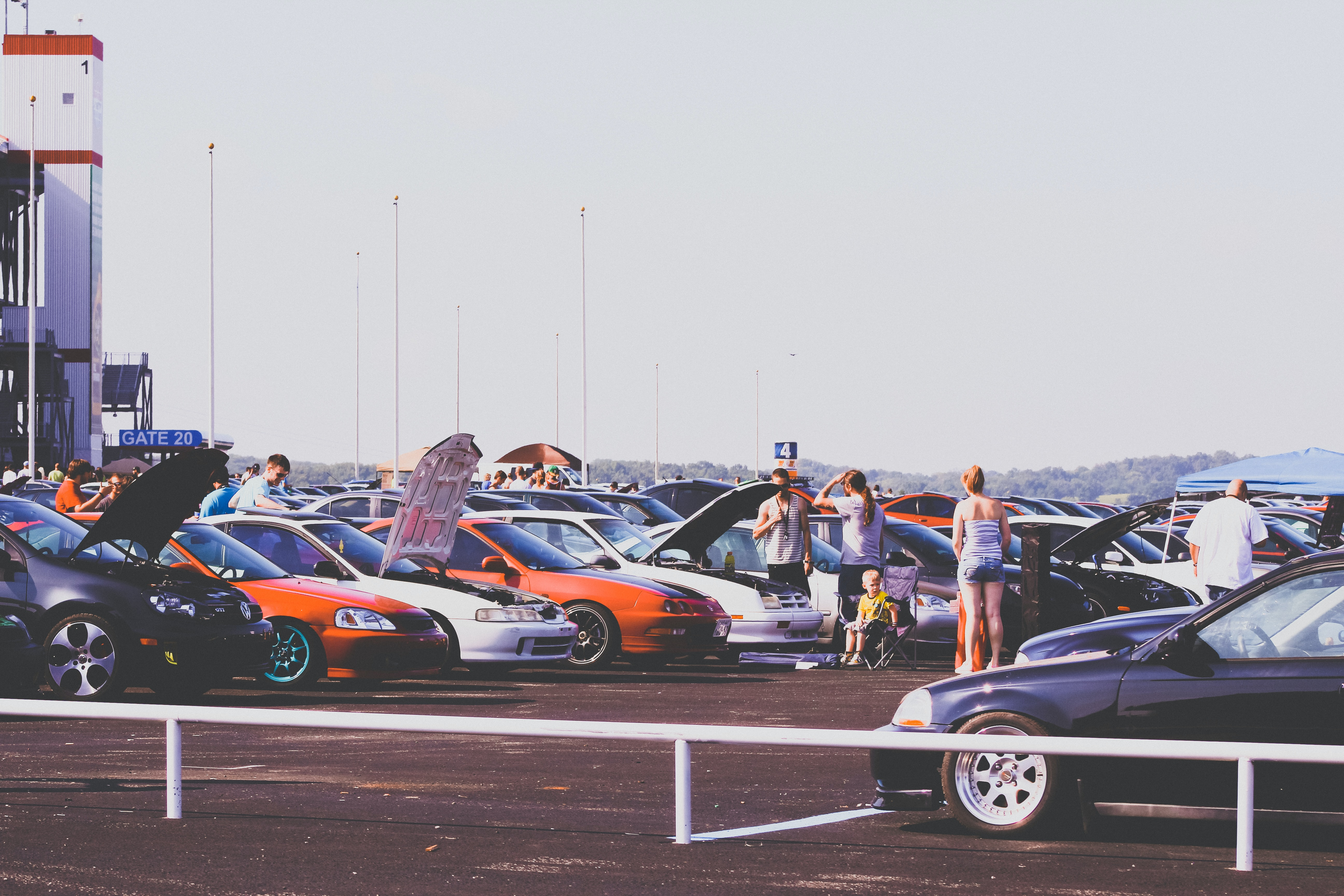People looking at cars parked in parking lot at a car show