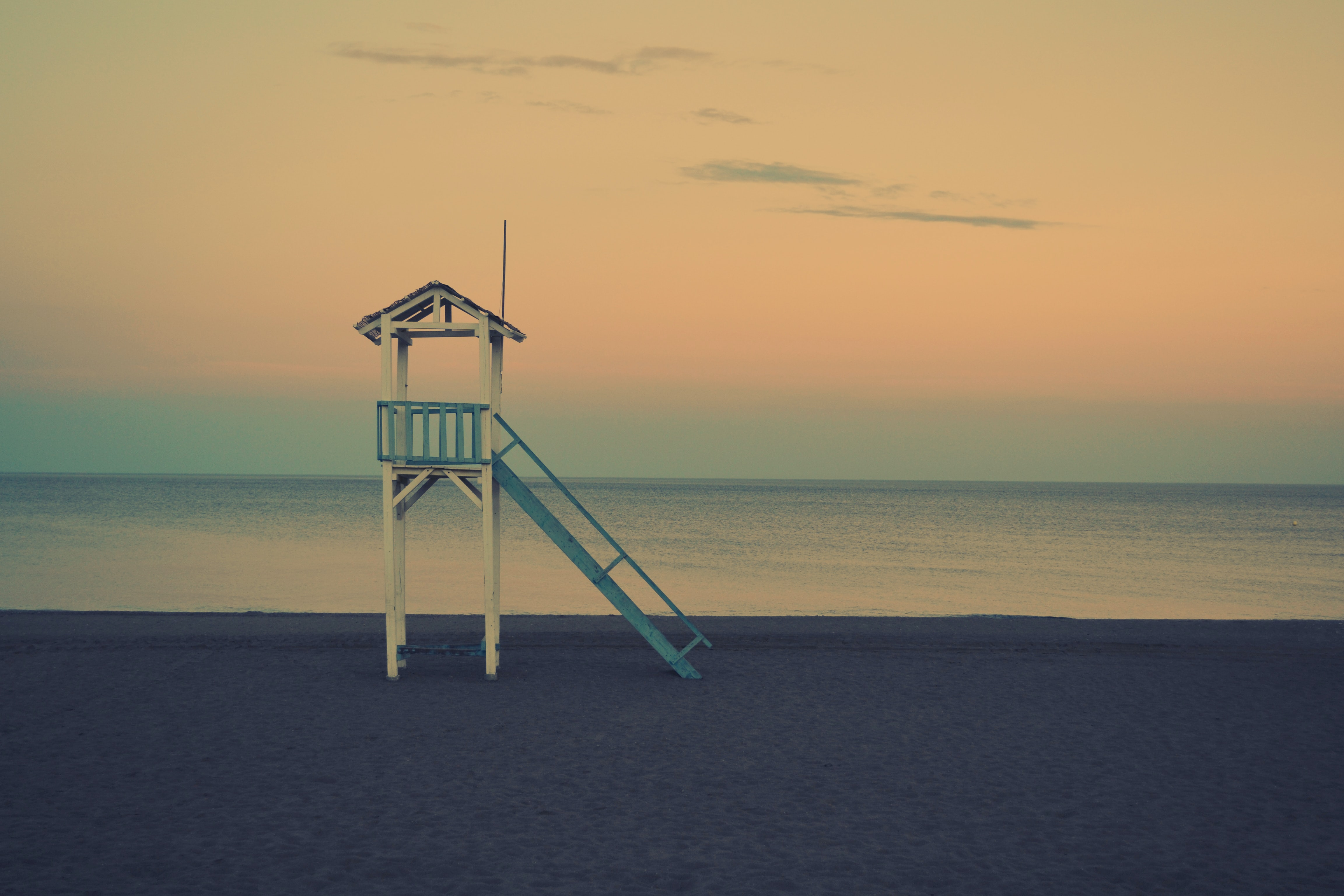 white wooden lifeguard station near seashore at golden hour