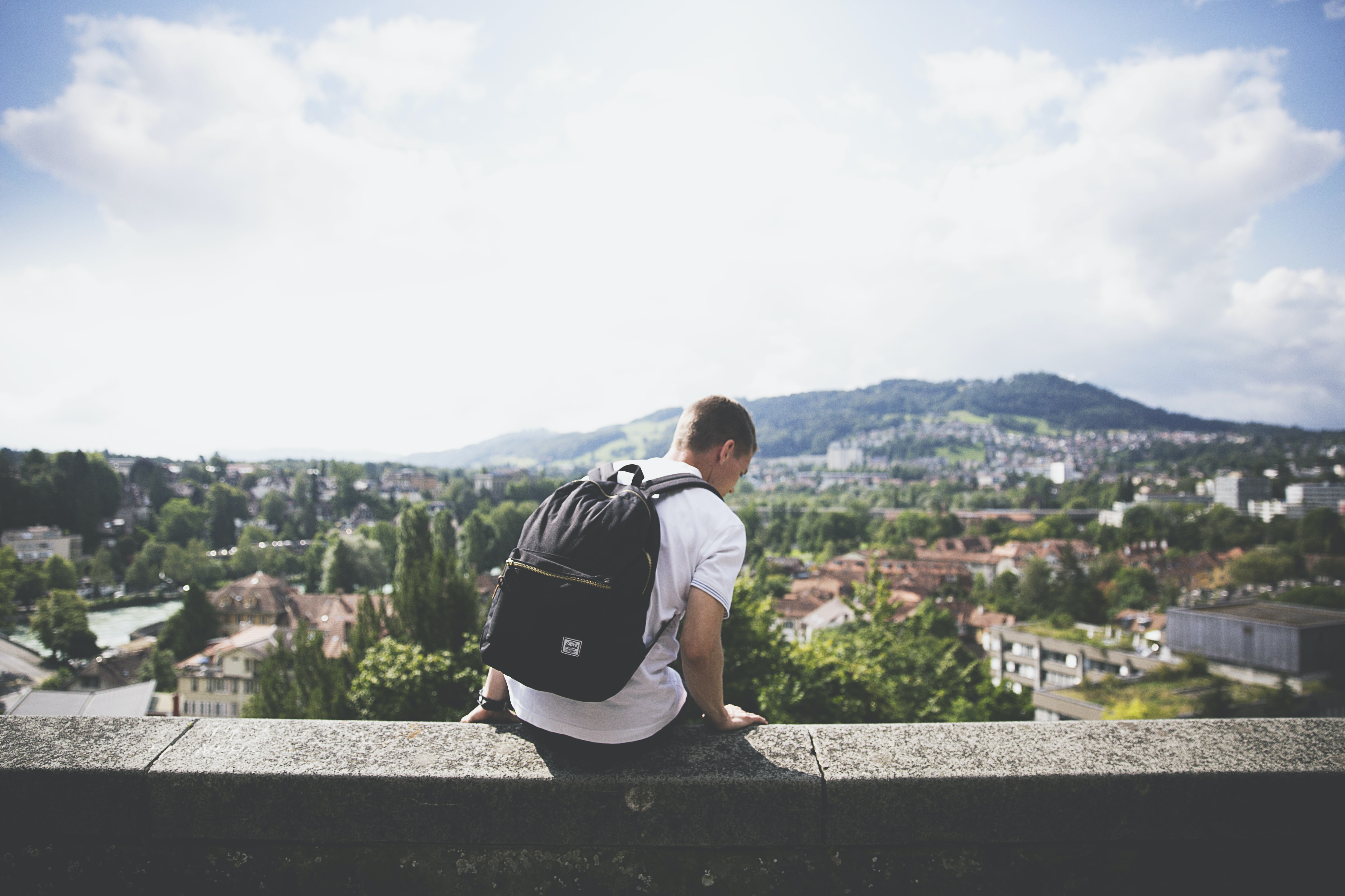 A man with a backpack sitting on a ledge overlooking a picturesque town