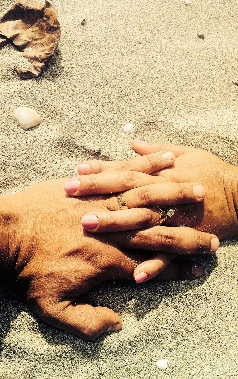 A married couple at the beach, wearing wedding rings, holds hands on the sand