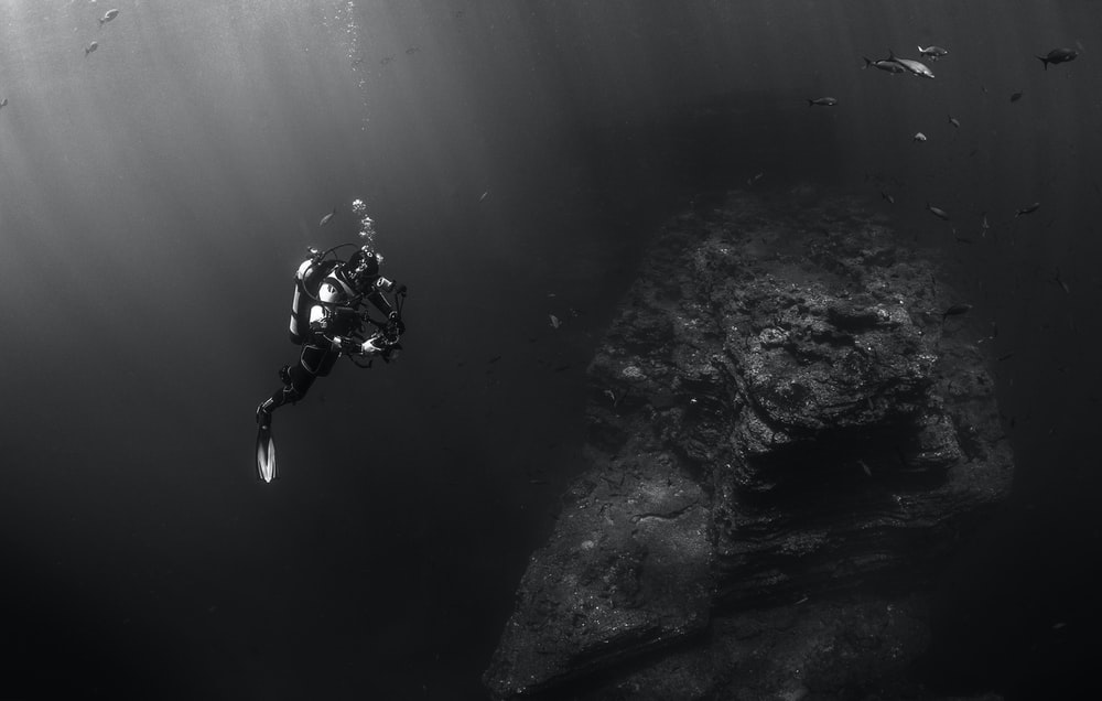 grayscale photo of person scuba diving