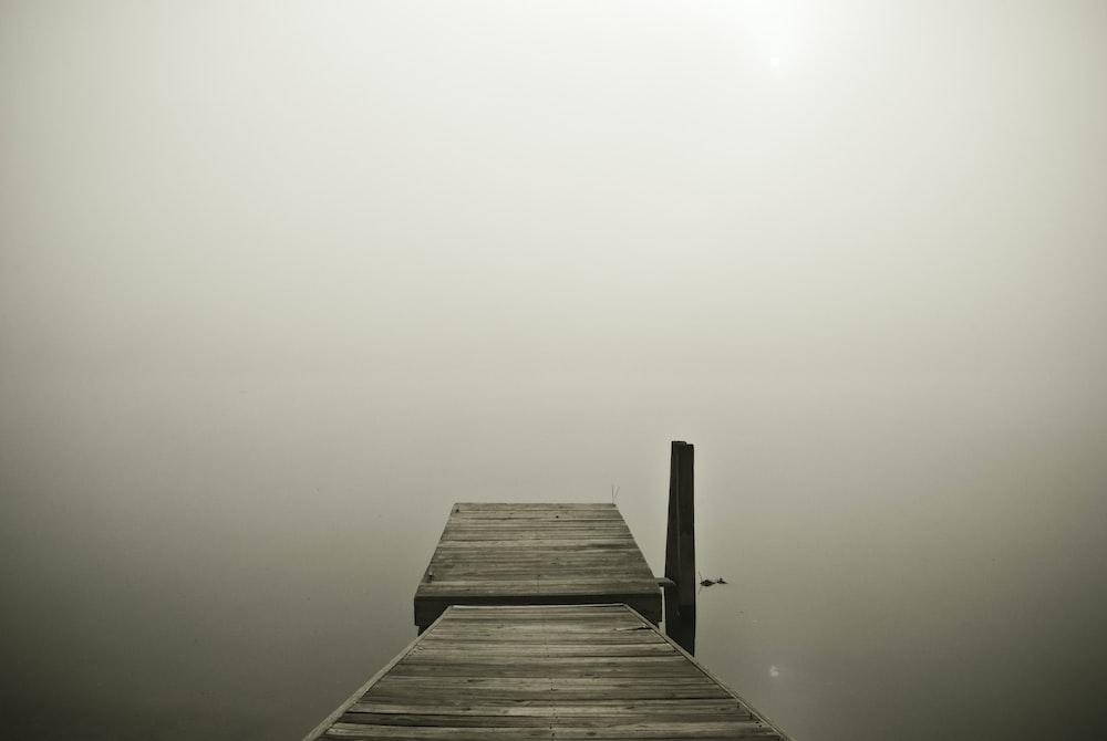 brown wooden pier on cloudy horizon