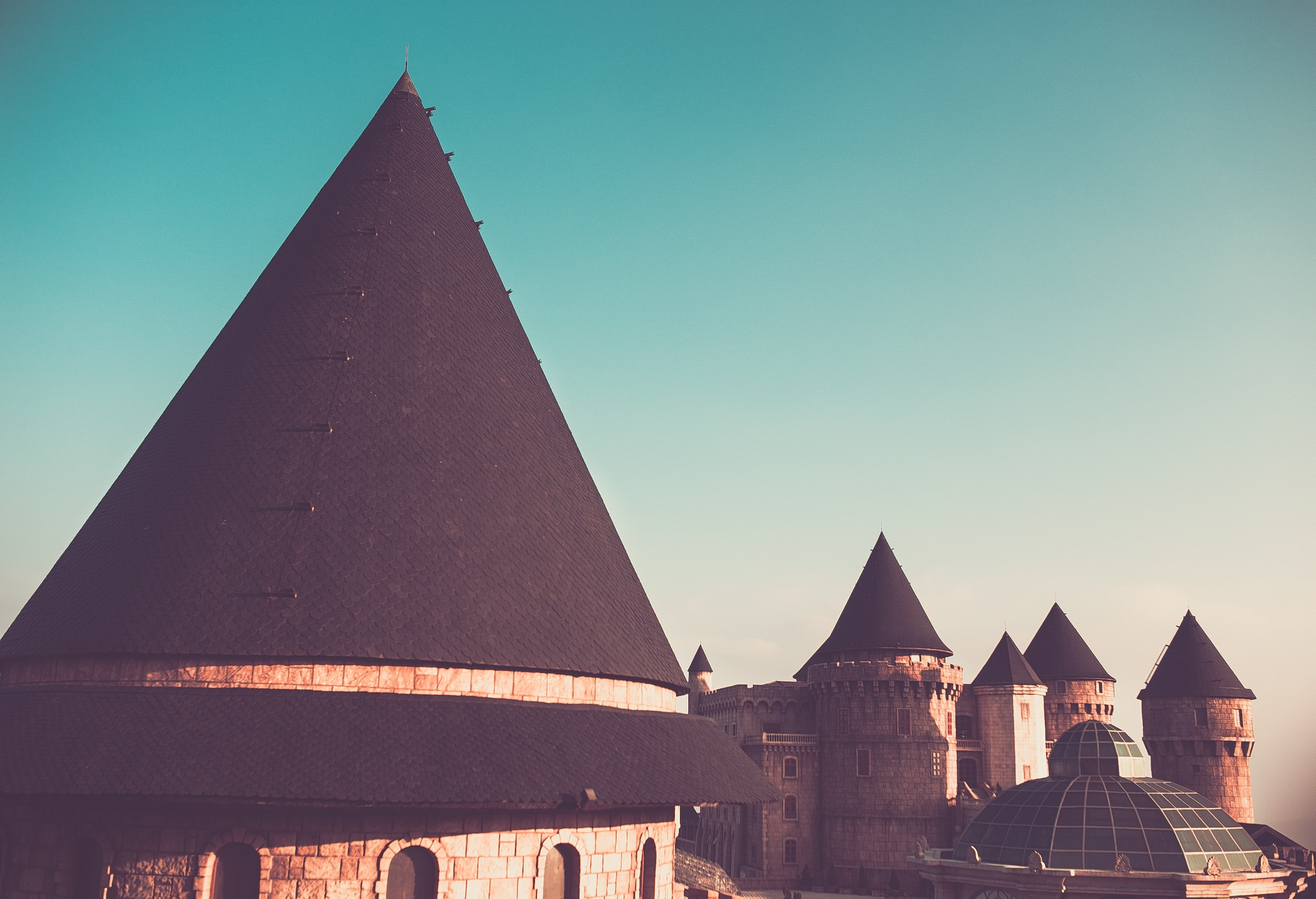 Cone rooftops of a castle building against a blue sky