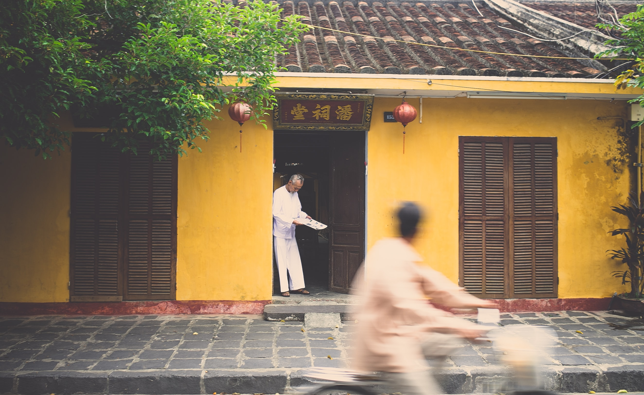 Asian house with a man in the door and another man on a bike driving by